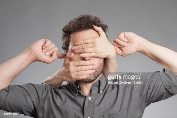 Cropped Image Of Hand Covering Man Eyes Against White Background