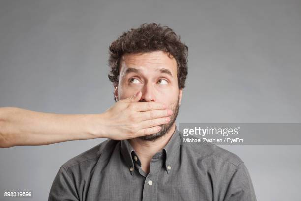 cropped image of hand covering man mouth against white background - hands covering mouth stock pictures, royalty-free photos & images