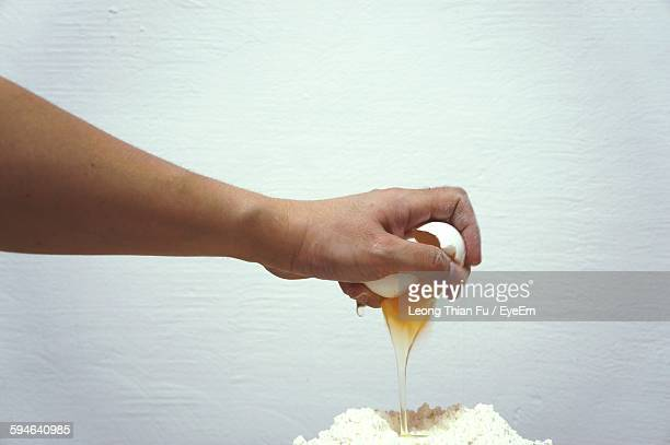 Cropped Image Of Hand Cracking Egg Over Flour Against White Wall