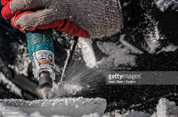 Cropped Image Of Hand Drilling On Ice