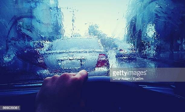 Cropped Image Of Hand Driving Car On Road In Rain