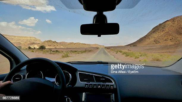cropped image of hand driving car - windshield stock pictures, royalty-free photos & images