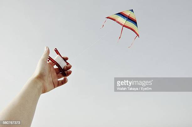 Cropped Image Of Hand Flying Kite