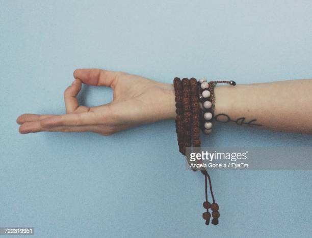 Cropped Image Of Hand Gesturing Mudra Against Blue Background
