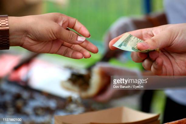 cropped image of hand giving currency to woman - barulho stock pictures, royalty-free photos & images