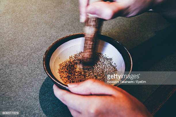 Cropped Image Of Hand Grinding Spices In Mortar And Pestle