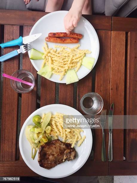 Cropped Image Of Hand Having Food In Plate On Table