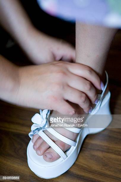 Cropped Image Of Hand Helping Girl In Wearing Sandal