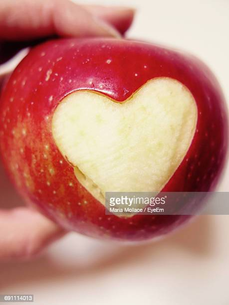 Cropped Image Of Hand Holding Apple With Heart Shape