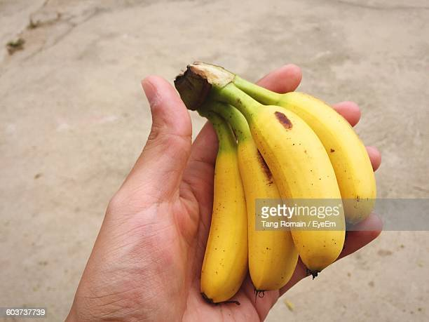 Cropped Image Of Hand Holding Bananas