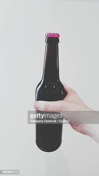 Cropped Image Of Hand Holding Beer Bottle Against White Background
