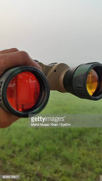 Cropped Image Of Hand Holding Binoculars