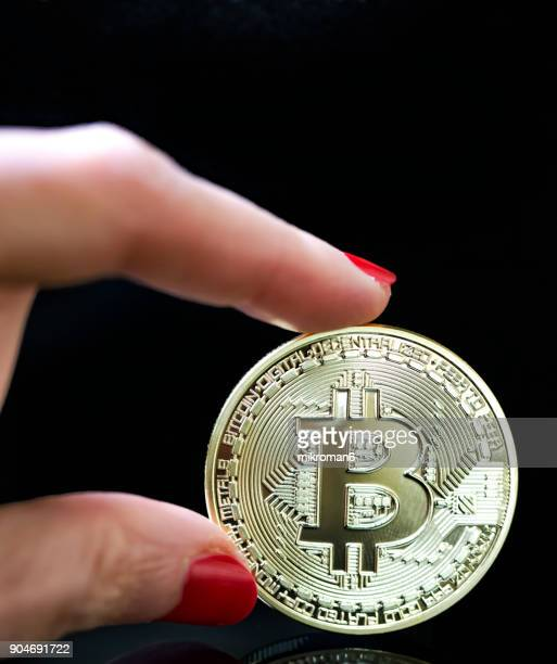 Cropped Image Of Hand Holding Bitcoin coin