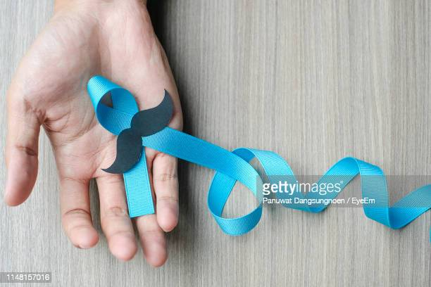 cropped image of hand holding blue ribbon with mustache on table - blue cancer ribbon stock photos and pictures