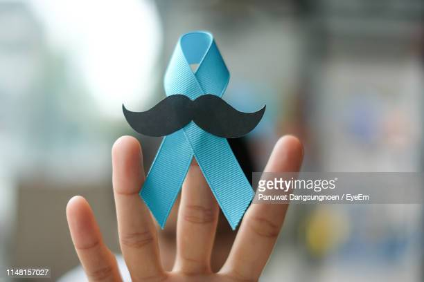 cropped image of hand holding blue ribbon with mustache - blue cancer ribbon stock photos and pictures