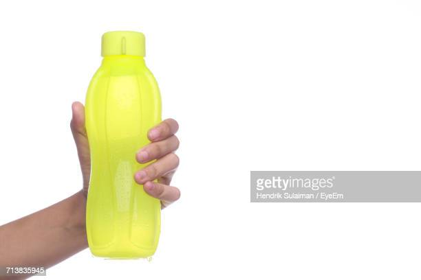 Cropped Image Of Hand Holding Bottle Against White Background