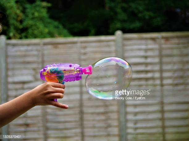 cropped image of hand holding bubbles against blurred background - bubble stock pictures, royalty-free photos & images