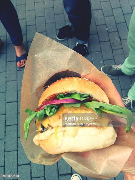 Cropped Image Of Hand Holding Burger On Street
