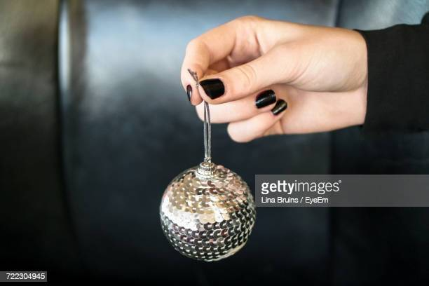 cropped image of hand holding christmas bauble - black nail polish stock photos and pictures
