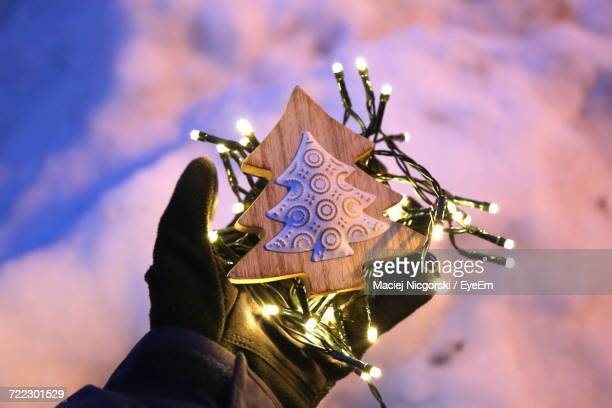 Cropped Image Of Hand Holding Christmas Tree Ornament And Illuminated String Lights