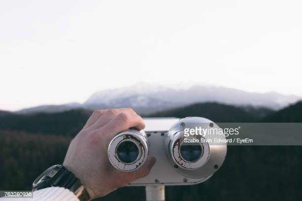 Cropped Image Of Hand Holding Coin-Operated Binoculars Against Mountain