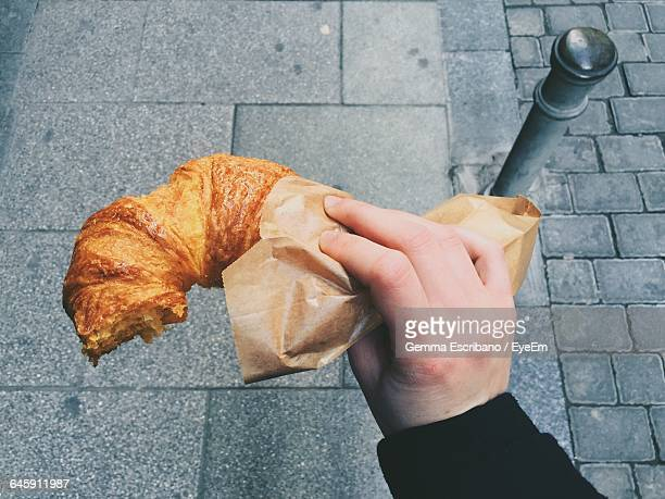 Cropped Image Of Hand Holding Croissant On Footpath