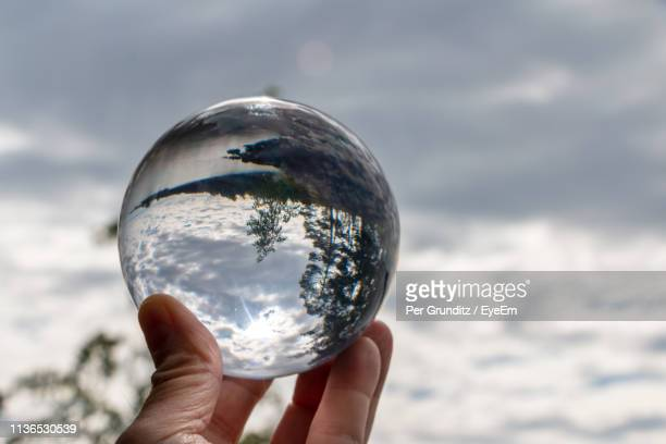 Cropped Image Of Hand Holding Crystal Ball Against Cloudy Sky