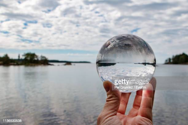 Cropped Image Of Hand Holding Crystal Ball Against Lake And Cloudy Sky