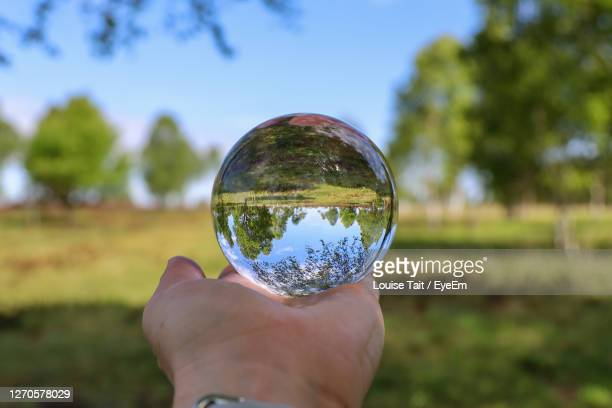 cropped image of hand holding crystal ball on field - china: through the looking glass stock pictures, royalty-free photos & images