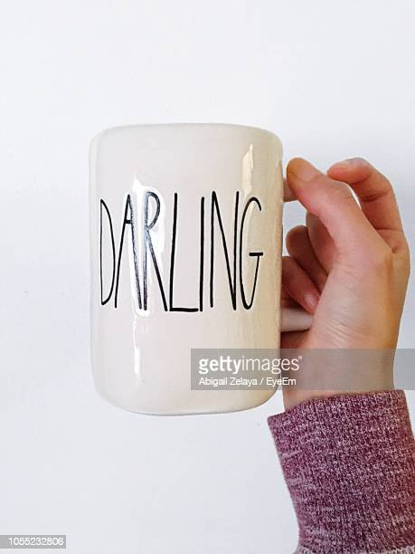 Cropped Image Of Hand Holding Cup With Text Against White Background