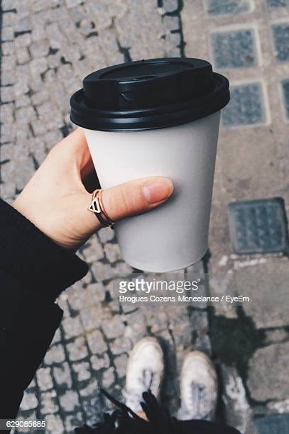 Cropped Image Of Hand Holding Disposable Cup On Street