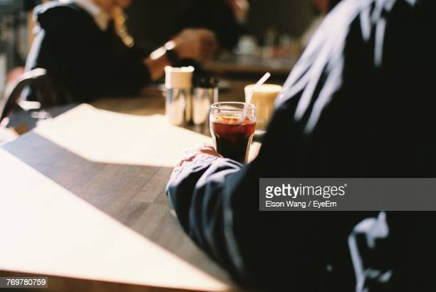 Cropped Image Of Hand Holding Drink At Cafe