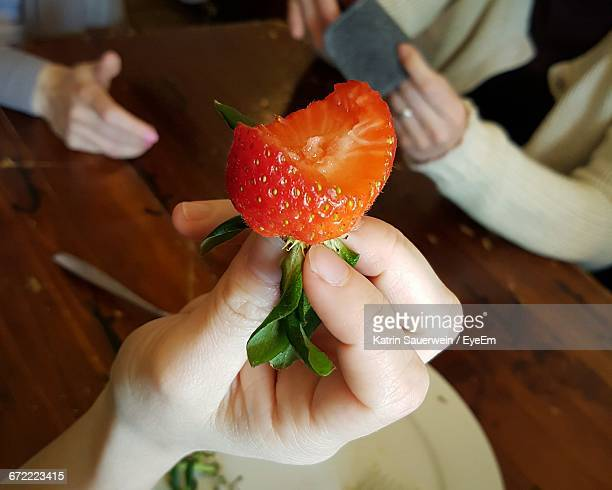 Cropped Image Of Hand Holding Eaten Strawberry
