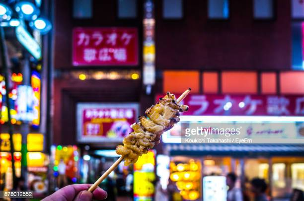 Cropped Image Of Hand Holding Food On Skewer At Market