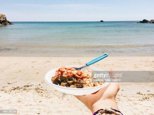 Cropped Image Of Hand Holding Food Plate In Front Of Sea At Beach