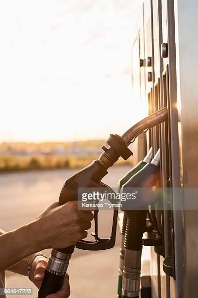 Cropped image of hand holding fuel pump at gas station