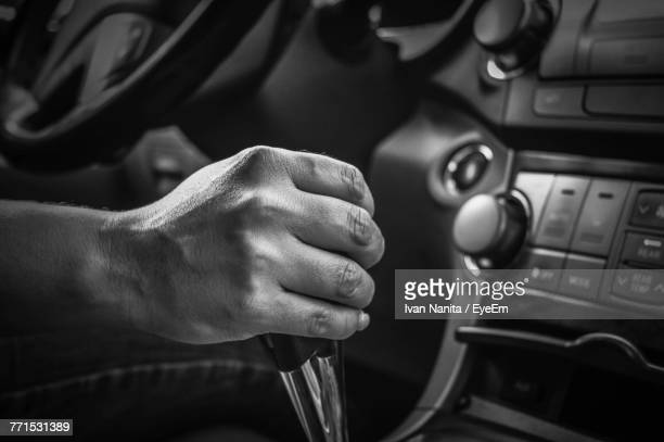 cropped image of hand holding gearshift - gearshift stock photos and pictures