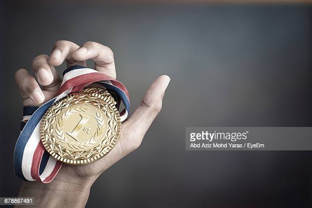 cropped image of hand holding gold medal against colored background - medalist stock pictures, royalty-free photos & images
