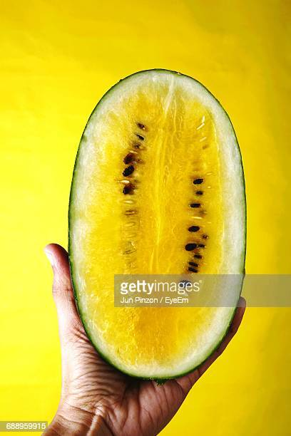 Cropped Image Of Hand Holding Halved Yellow Watermelon Against Colored Background