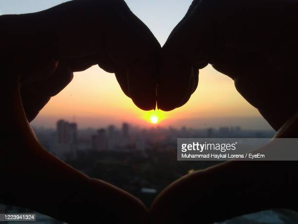 cropped image of hand holding heart shape against sky during sunset - lorena day stock pictures, royalty-free photos & images