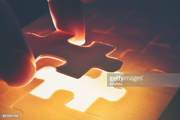 Cropped Image Of Hand Holding Illuminated Jigsaw Puzzle