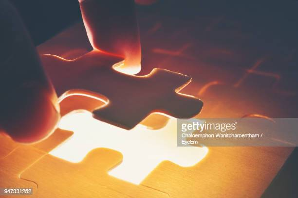 cropped image of hand holding illuminated jigsaw puzzle - puzzle stock-fotos und bilder