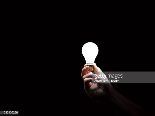 cropped image of hand holding illuminated light bulb against black background - light bulb stock pictures, royalty-free photos & images