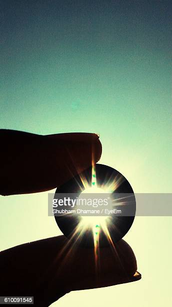 Cropped Image Of Hand Holding Lens Against Bright Sun