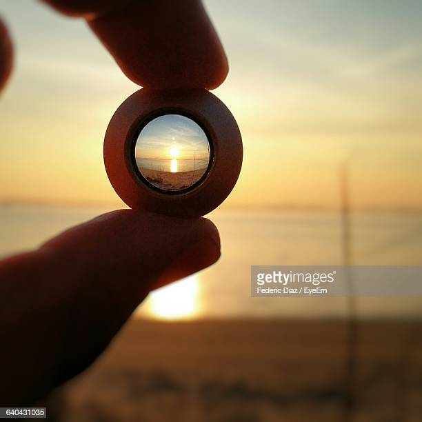 Cropped Image Of Hand Holding Lens Against Sea During Sunset