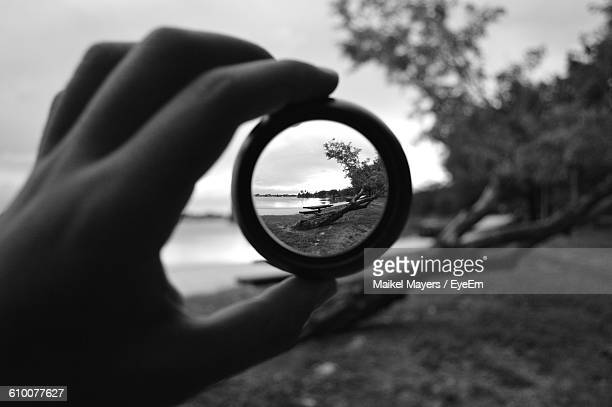 Cropped Image Of Hand Holding Lens Against Trees On Lakeshore