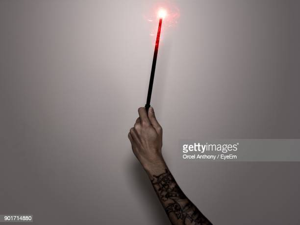 cropped image of hand holding magic wand against wall - 手品師の杖 ストックフォトと画像