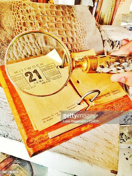 Cropped Image Of Hand Holding Magnifying Glass Over Calendar On Table