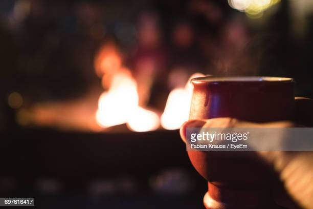 cropped image of hand holding mulled wine cup by campfire at night - one night stand stock-fotos und bilder