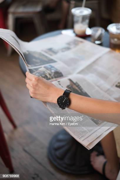 Cropped Image Of Hand Holding Newspaper